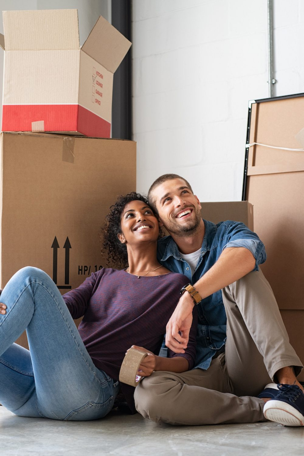 Young couple resting after moving into a new home and daydreaming. Multiethnic contemplative couple sitting on floor and thinking about their future while looking up. Happy married couple buy new apartment and plan a family.