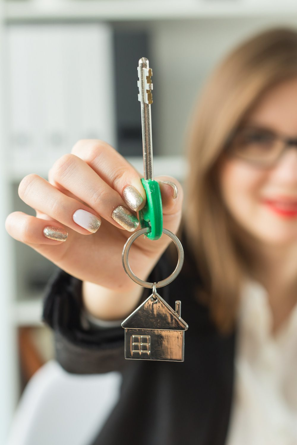 New home and real estate concept - Close up of happy realtor woman with red lips giving you keys from new apartment.